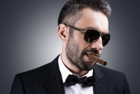 Bossy and self-confident. Portrait of handsome mature man in formalwear and sunglasses smoking cigar and looking away while standing against grey background