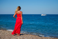 Beautiful girl in red dress on th beach