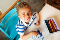 Preschooler Playing with a Box of Crayons