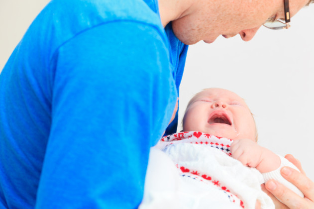 Newborn baby crying in father's hands