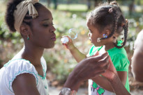 Mother blowing soap bubbles with her two daughters