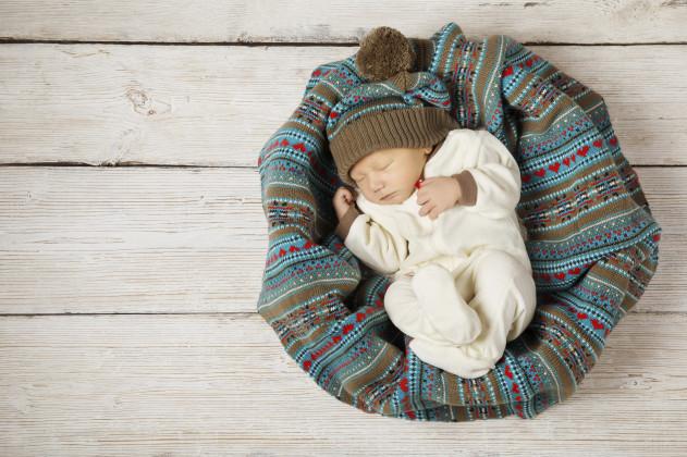 baby newborn sleeping in woolen hat on white wooden background,