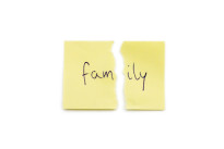 Yellow paper note torn in two with the word family, isolated on