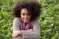 Smiling mixed race woman sitting on grass