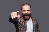 Hey you! Furious young bearded man pointing you and shouting while standing against grey background