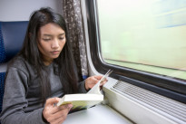 Young woman reading a book on the train