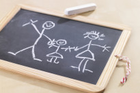 child's drawing on a chalkboard depicting a family