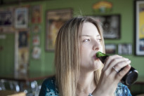 Blonde Woman with Beautiful Blue Eyes Drinks a Bottle of Beer