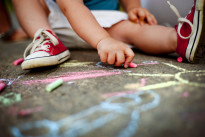 Close up of boy drawing with chalks