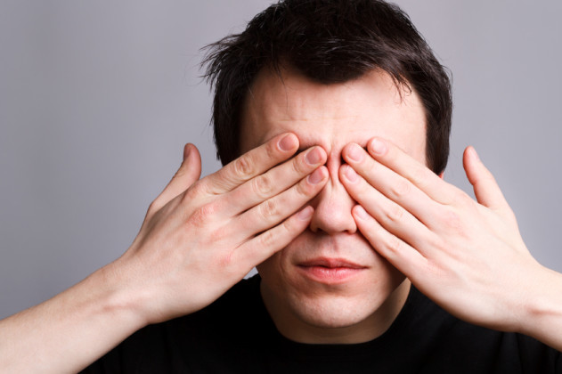 young man closes his eyes with his hands