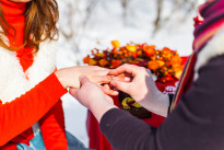 man putting wedding ring on woman hand. Christmas and New Year decoration