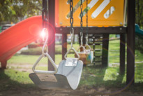 Playground swing set with lens flare (selective focus)