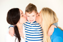 Female couple kissing son's cheeks