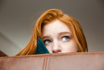 Unconfident shy redhead girl peeping from sofa