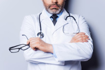 Confidence and experience. Close-up of mature grey hair doctor keeping arms crossed and holding eyeglasses while standing against grey background