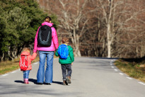 mother and kids with backpacks walking on the road