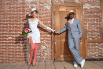 Vintage jazz fashion sexy wedding couple in old urban building. Mixed race. Wearing a hat.
